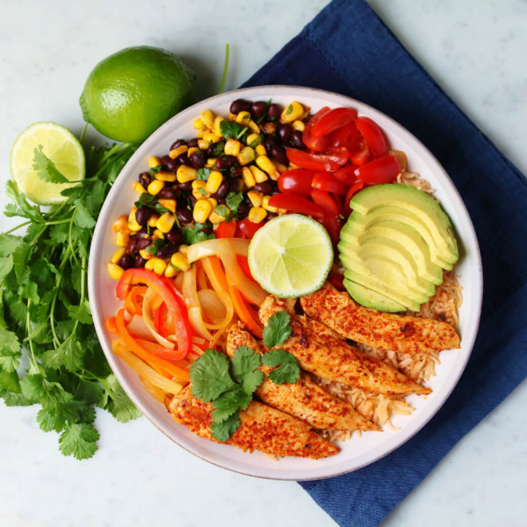 Simply Delicious Chicken Burrito Bowl - a bowl filled with chicken, rice, peppers, avocado, corn and beans.