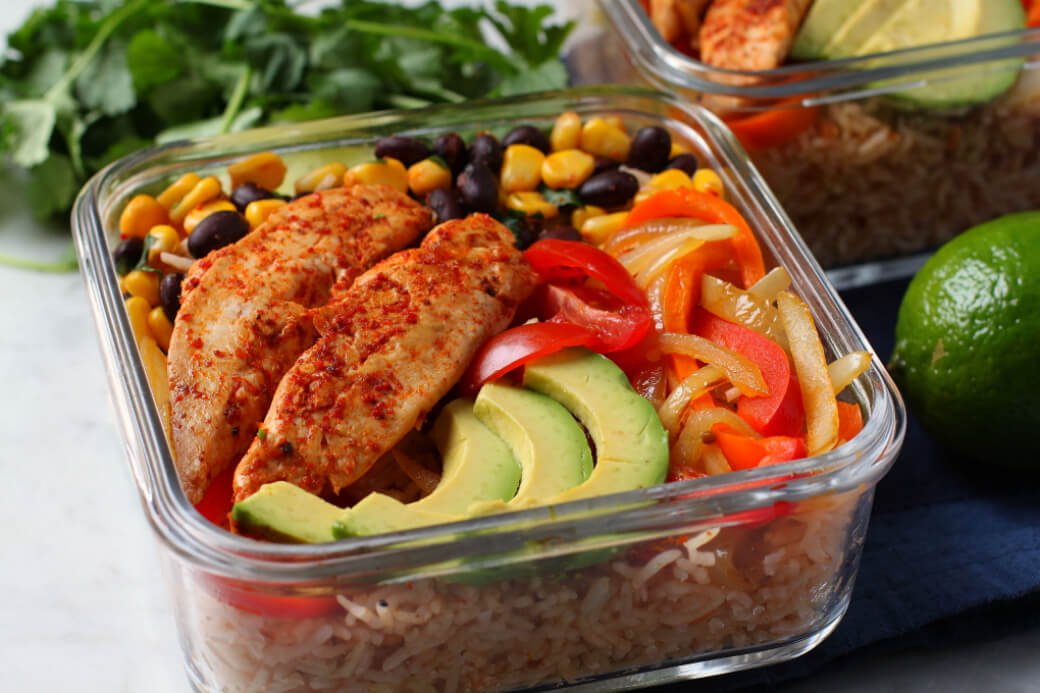 Simply Delicious Chicken Burrito Bowl - a square glass fridge container filled with chicken, rice, peppers, avocado, corn and beans.