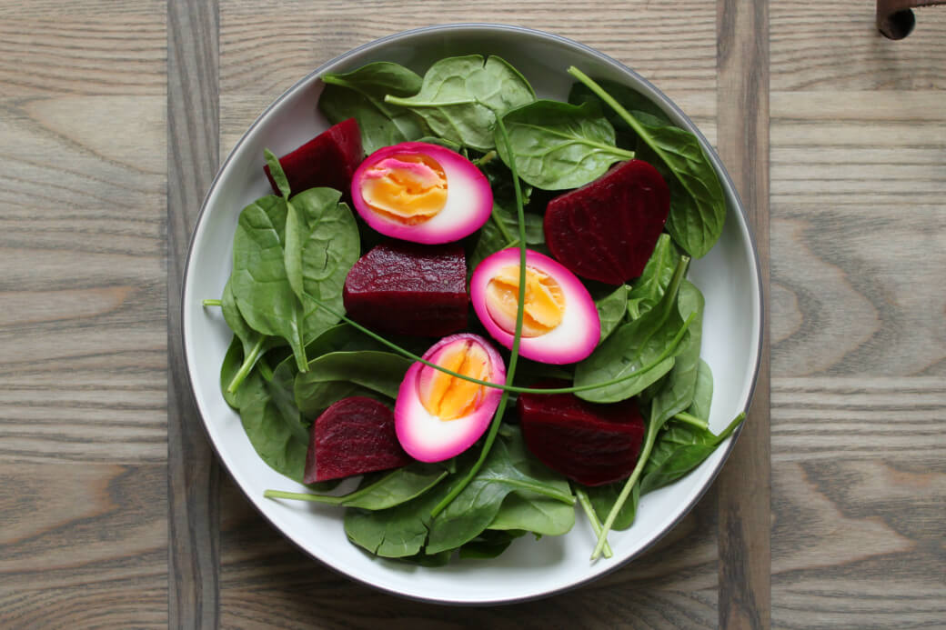 Pickled Egg and Beet Spinach Spring Salad - Dark red beets and bright pink stained eggs sit on top of a bed of green spinach.