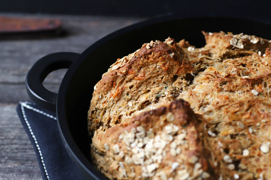 Cheesy Cheddar Stout Soda Bread - Close up of a golden baked soda bread showing cheese layers.