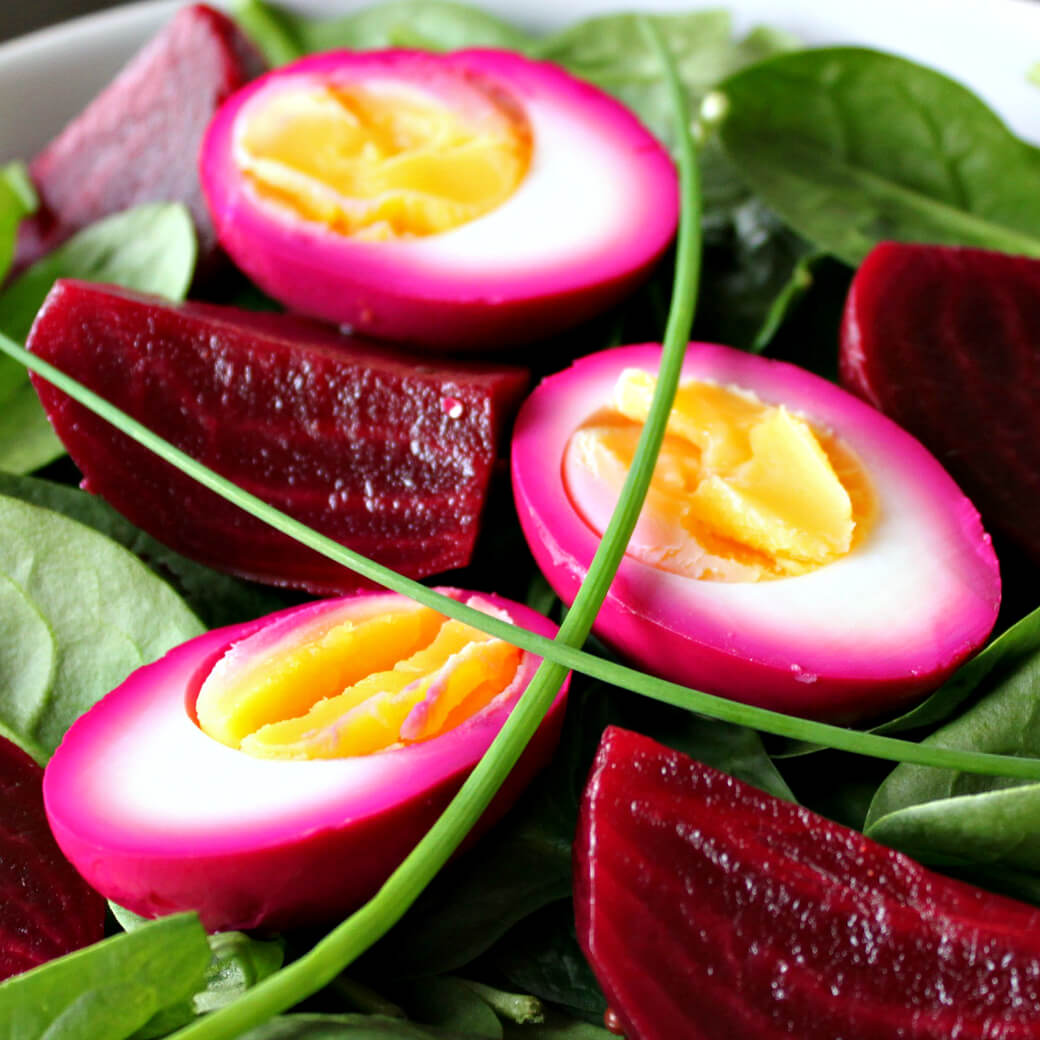Pickled Egg and Beet Spinach Spring Salad - Close up of dark red beets and bright pink stained eggs.