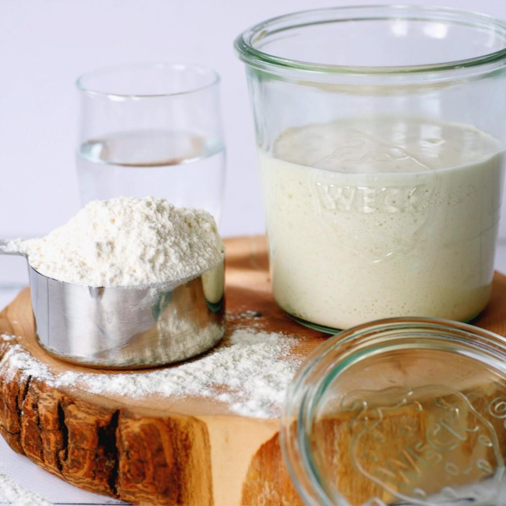 How to Make Sourdough Starter - sourdough starter in a glass jar surrounded by measuring cup of flour and jar of water.