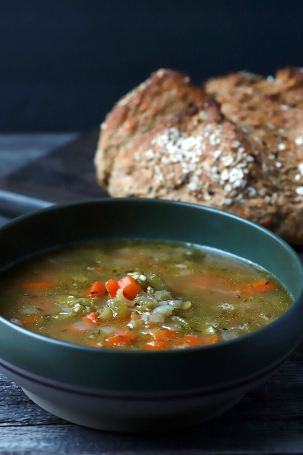 Split Pea and Ham Soup - A bowl of soup with ham, carrots, and onions with a soda bread in the background.