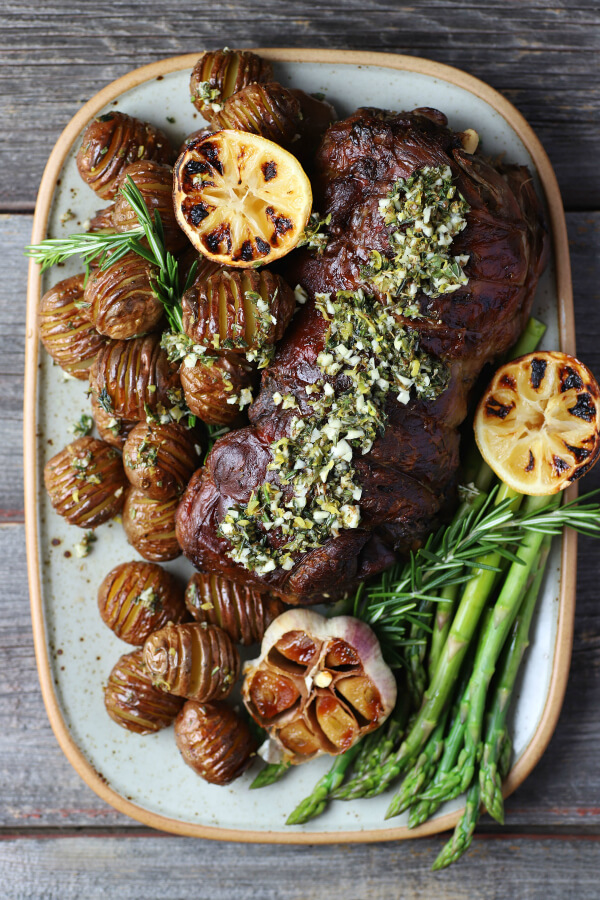 A platter filled with a boneless roasted leg of lamb, potatoes, asparagus, roaster garlic, and charred lemon.
