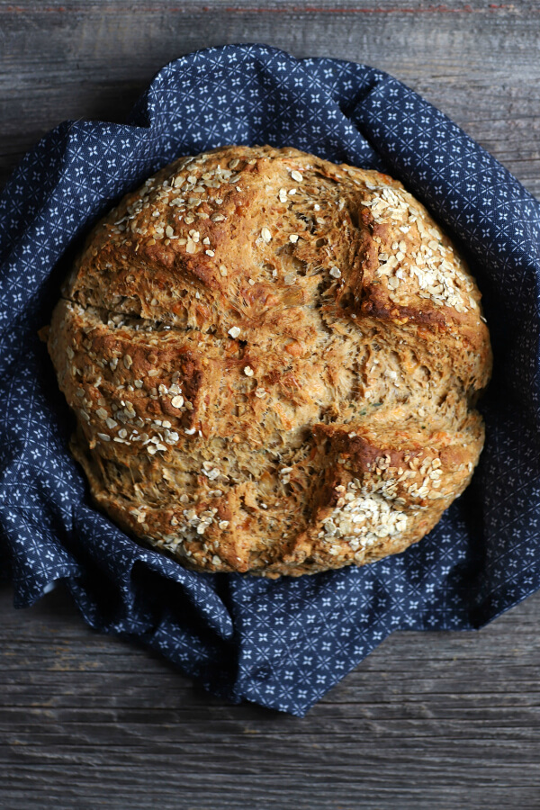 Cheesy Cheddar Stout Soda Bread - A golden baked boule of soda bread surrounded by a blue cloth.