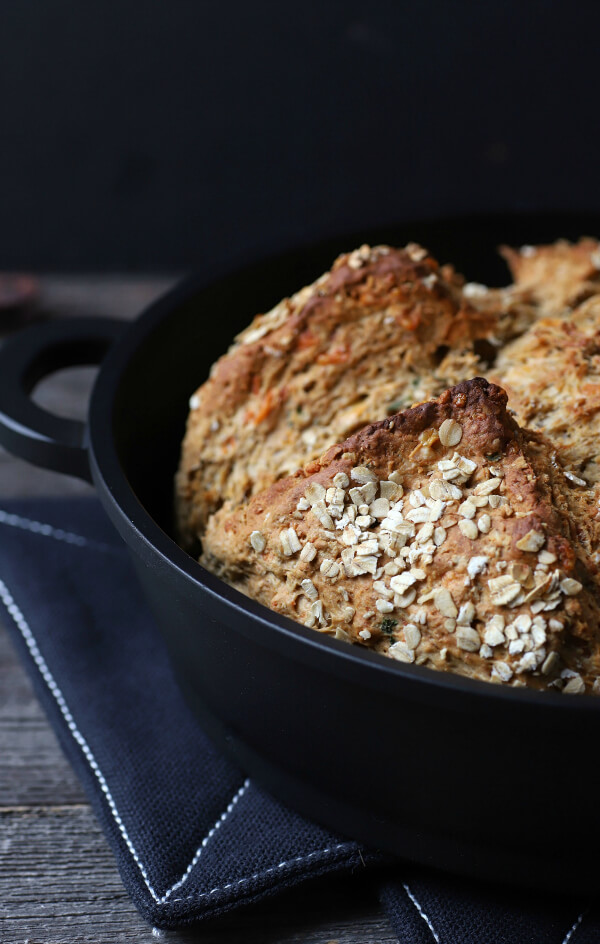 Cheesy Cheddar Stout Soda Bread - a golden baked soda bread in a cast iron pan on a wooden background