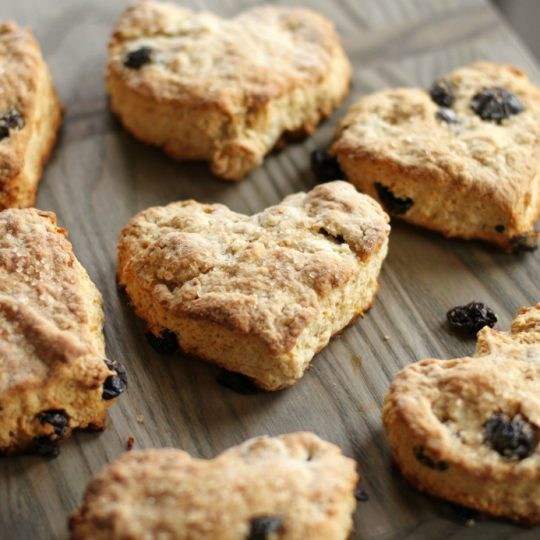 Cranberry Lemon Scones - Heart Shaped golden baked scones studded with red cranberries on a wooden board.
