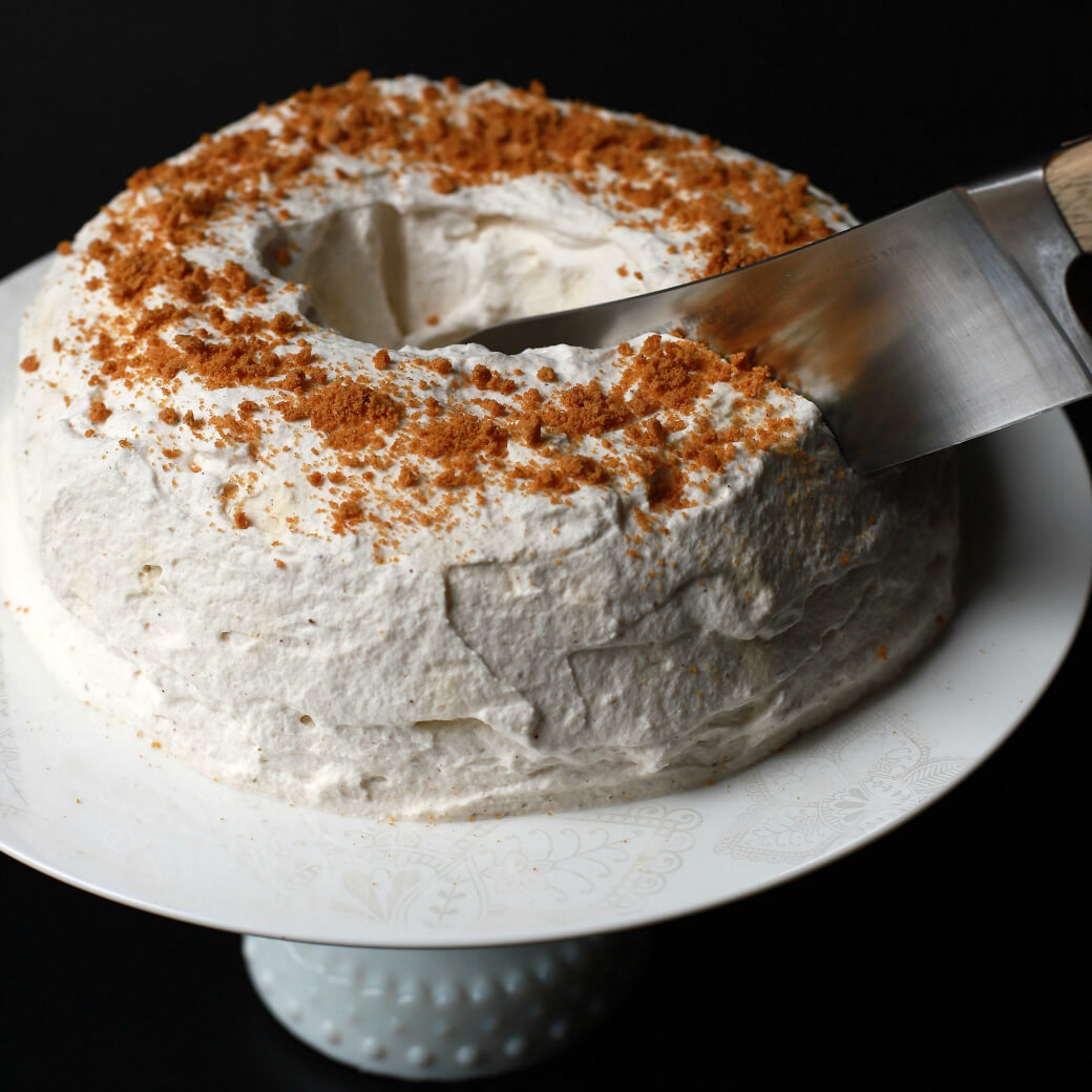 A knife cuts into a white circular cake topped with ginger crumbs.