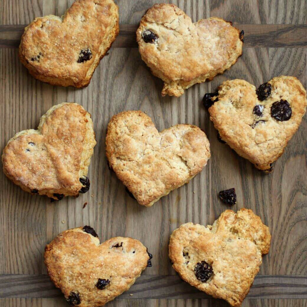 Cranberry Lemon Scones - Heart Shaped golden baked scones studdedwith red cranberries on a wooden board.
