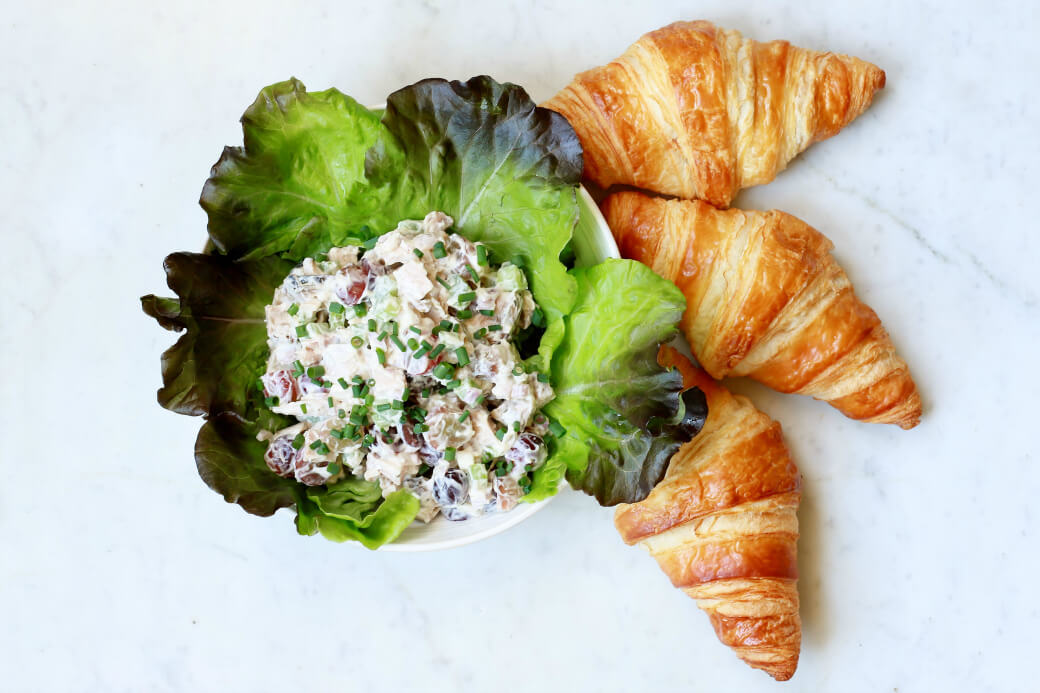 Three croissants and a lettuce lined bowl filled with chicken salad.