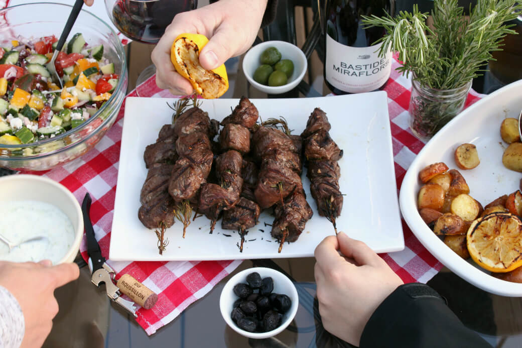 A hand squirts a bit of lemon over juicy grilled beef kabobs while another grabs a kabob.