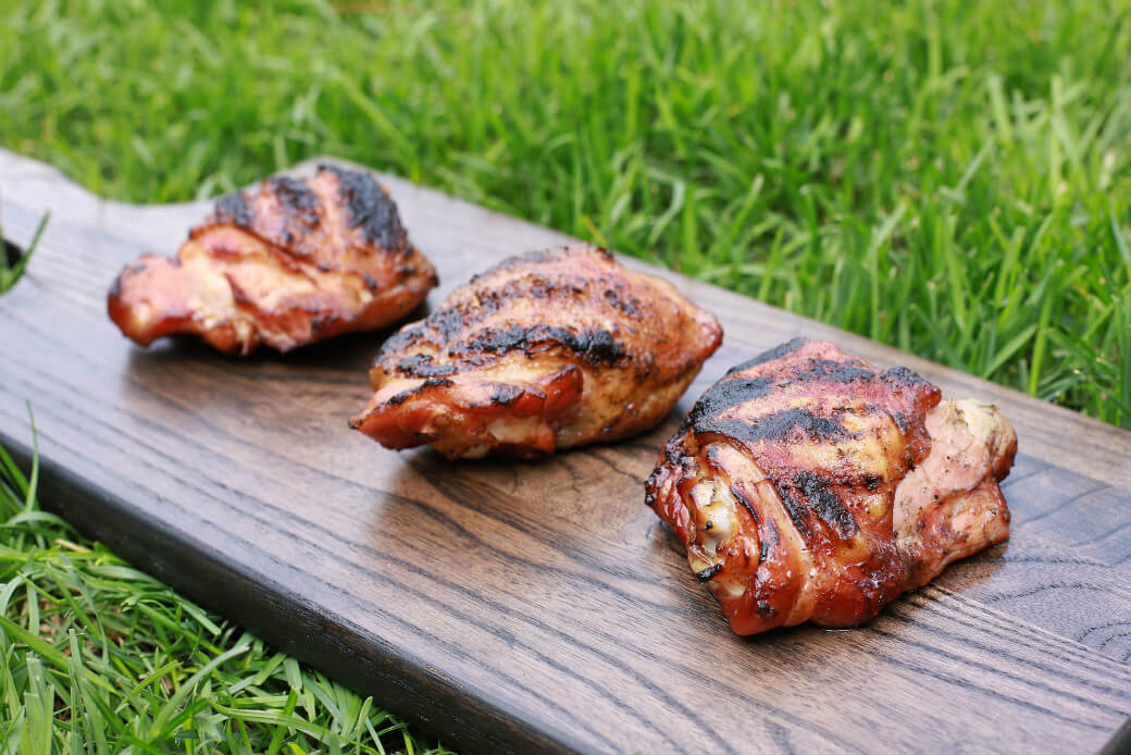 Three perfectly smoked and grilled chicken thighs on dark wooden board in the green grass.