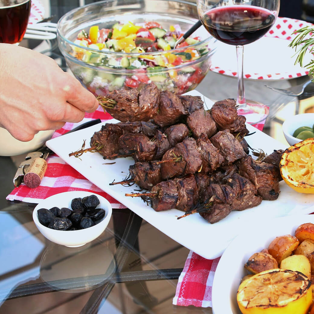 A hand holds a beef kabob over a platter of kabobs surrounded by wine and salad.