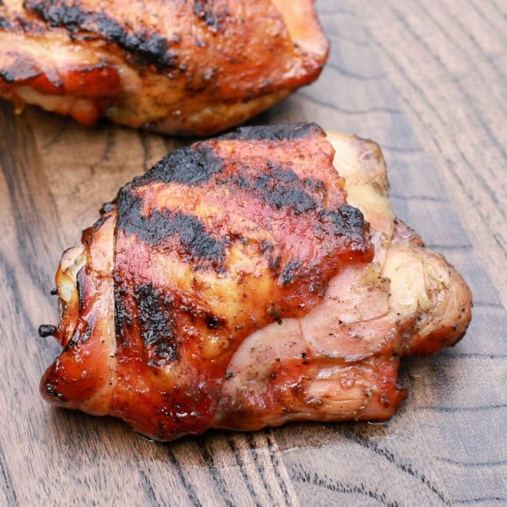 One perfectly smoked and grilled chicken thigh on dark wooden board.