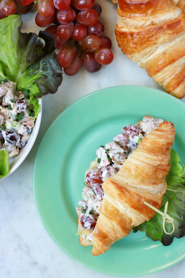 Three croissants, a bunch of red grapes, and a lettuce lined bowl filled with chicken salad. A made up chicken salad croissant sits on a green plate.