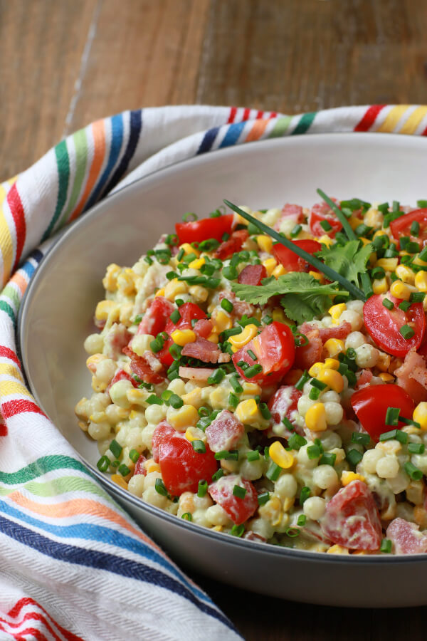 Smoked Corn Bacon Avocado Pasta Salad is a bright and cheerful salad containing red grape tomatoes, corn, bacon, cilantro, and pearl couscous in a white bowl.