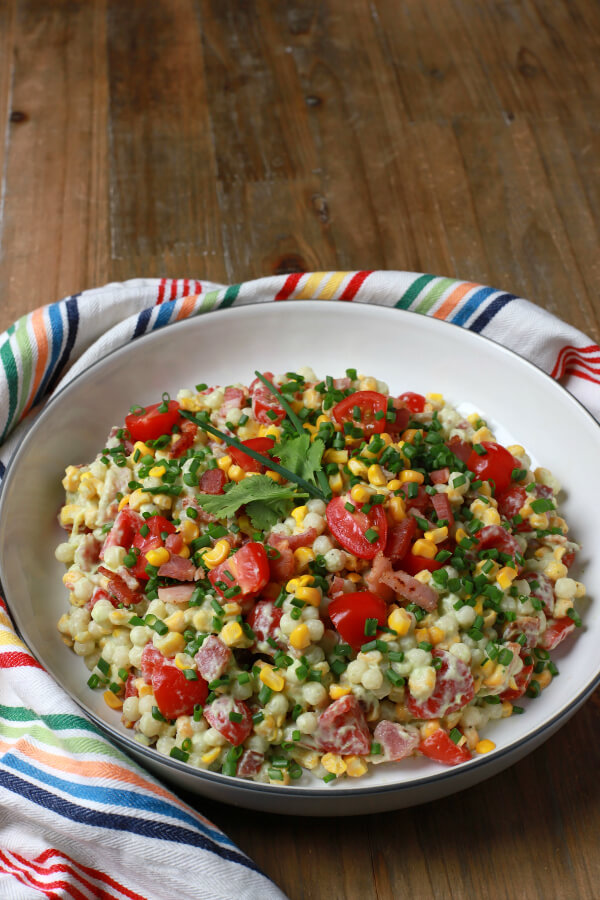 A bright and cheerful salad containing red grape tomatoes, corn, bacon, cilantro, and pearl couscous in a white bowl.