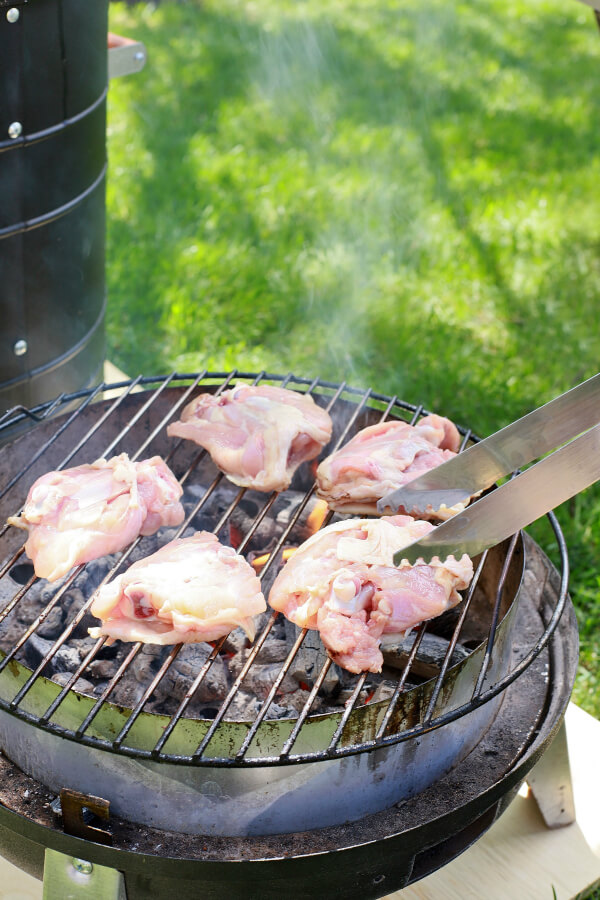 A pair of grilling tongs places raw chicken thighs on a hot grill.