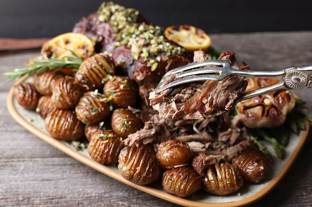 Silver tongs holding pulled lamb meat above a platter filled with a boneless roasted leg of lamb, potatoes, asparagus, roaster garlic, and charred lemon.
