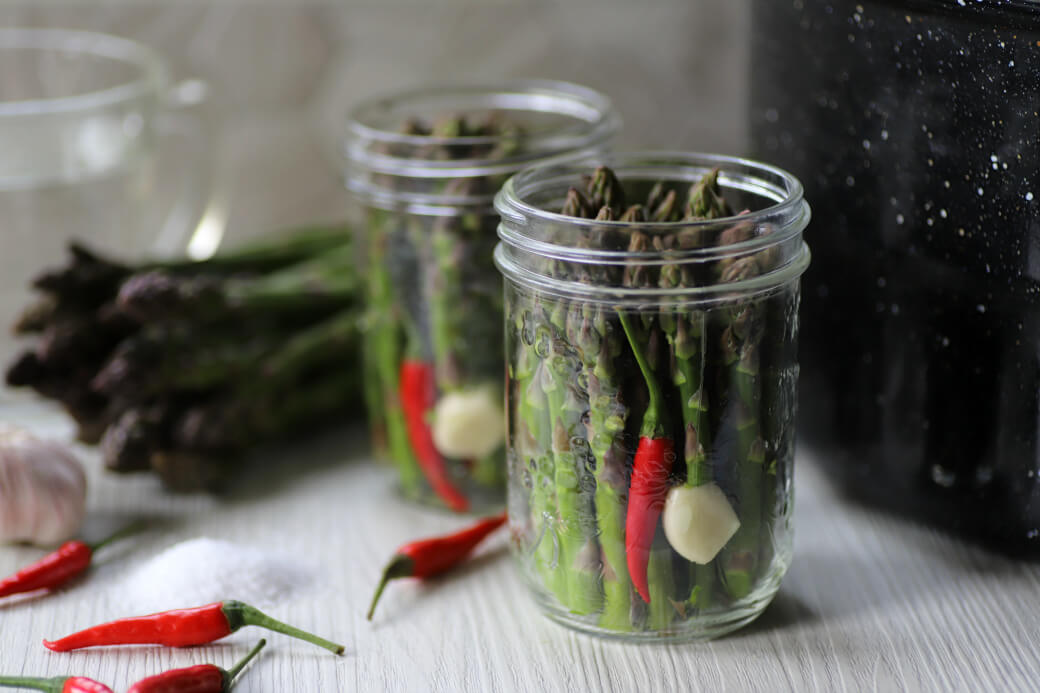 Two clear glass jars filled with green asparagus, a garlic clove, and a red hot pepper.