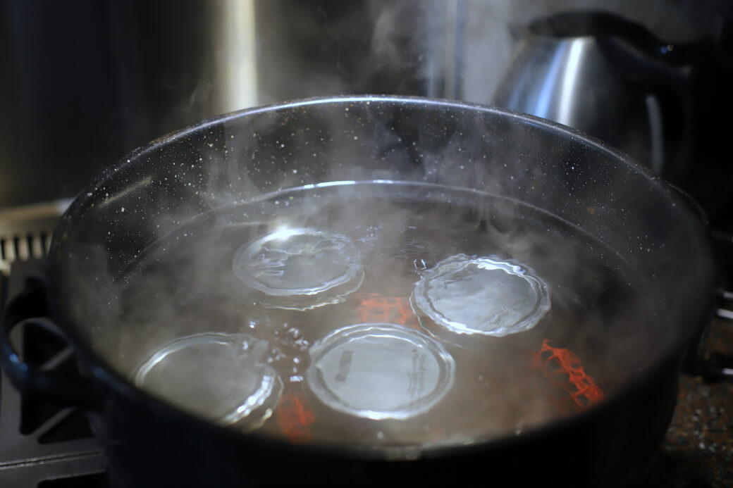 Jars of asparagus pickles being processed in a canner filled with boiling water.