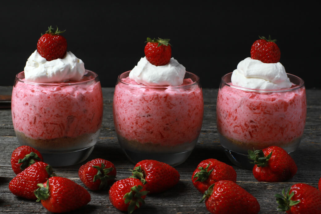 Three pink rhubarb strawberry jello desserts in cups with strawberries and cream.
