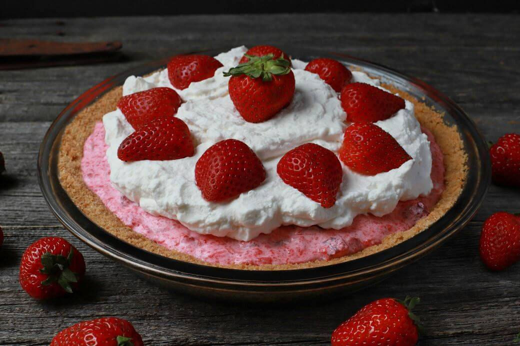 A pink rhubarb strawberry pie in a graham crust topped with strawberries and whipped cream.