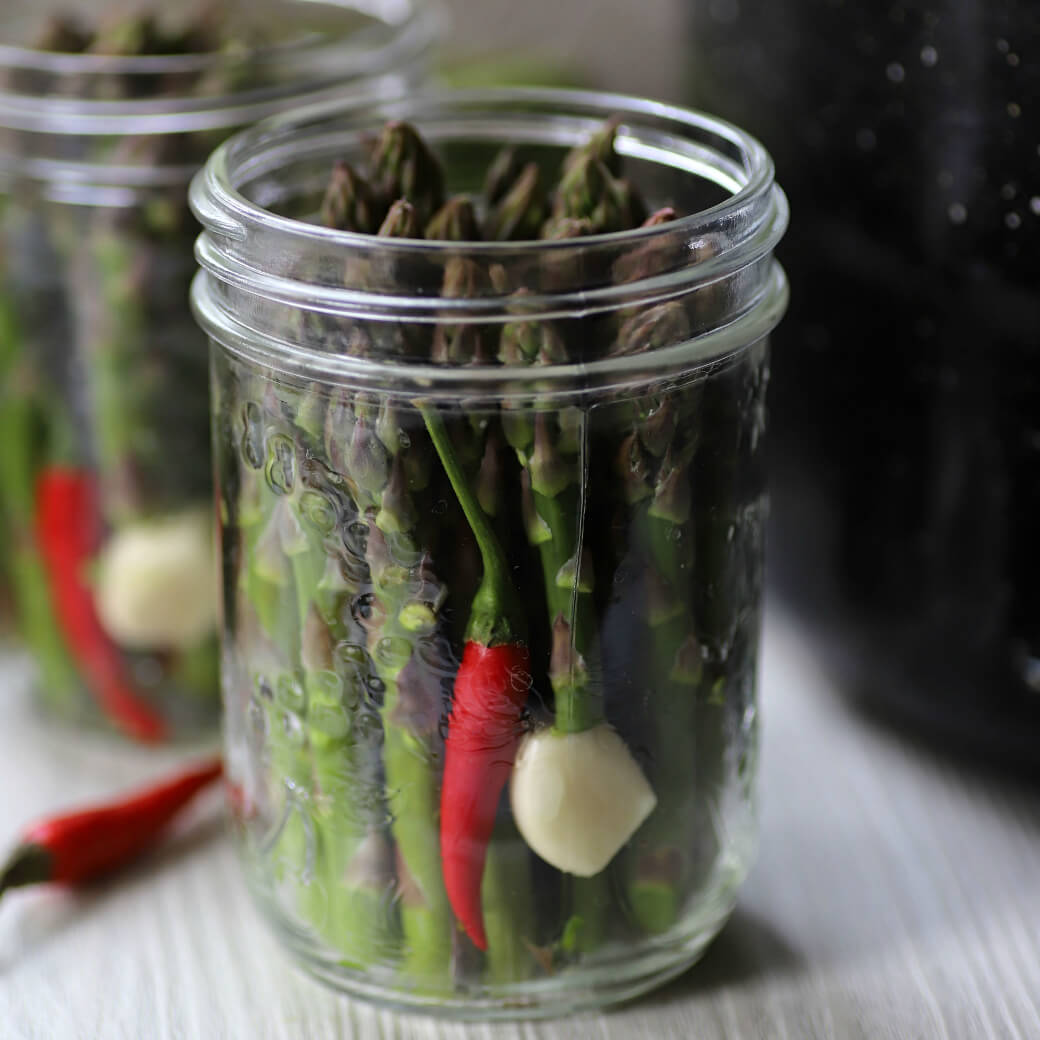 A clear glass jar filled with green asparagus, a garlic clove, and a red hot pepper.