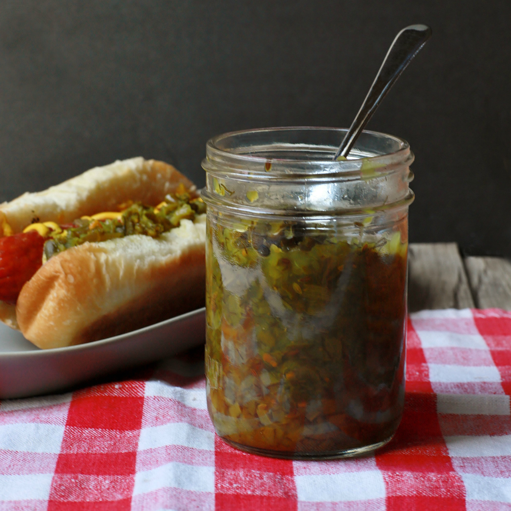 A jar of Garlic Scape Relish next to a loaded hot dog.