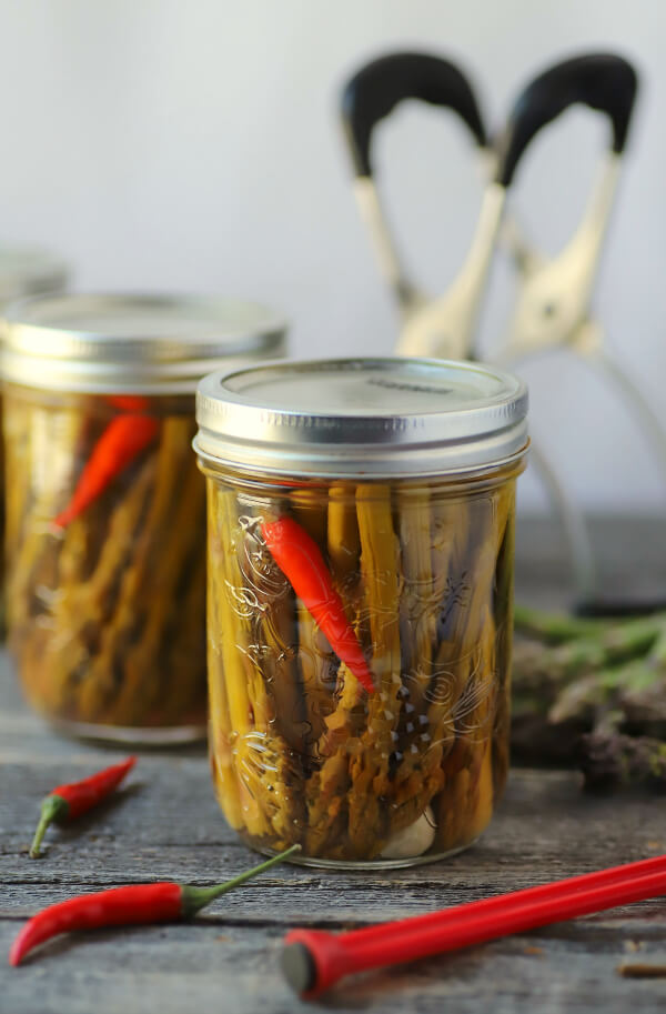 Two clear glass jars filled with green asparagus, a garlic clove, and a red hot pepper after processing in a hot water bath.
