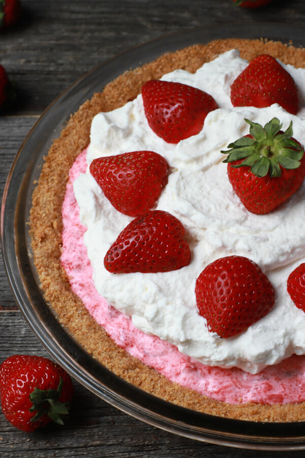 A pink pie in a graham crust topped with strawberries and whipped cream.