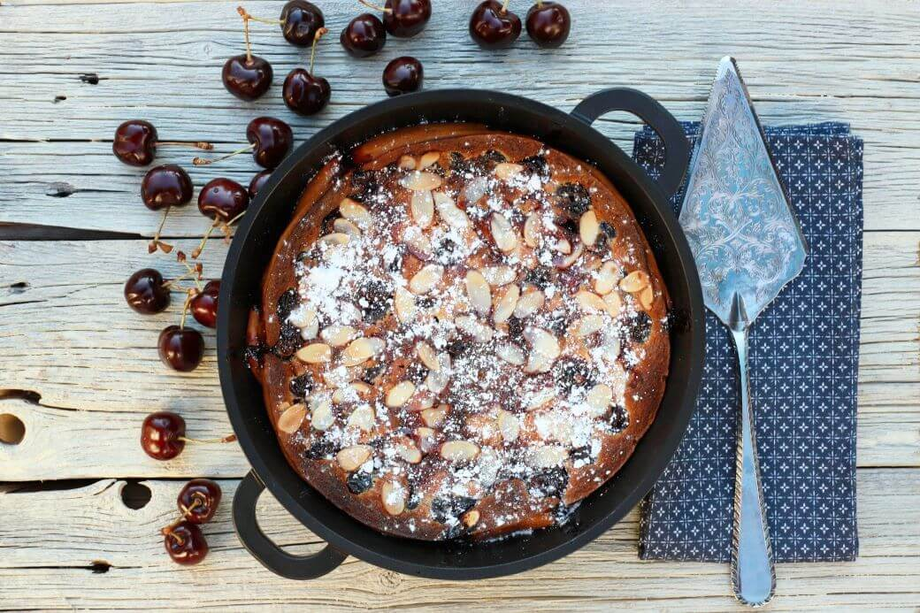 A cast iron pan containing baked cherry clafoutis topped with almonds and powdered sugar surrounded by fresh cherries.