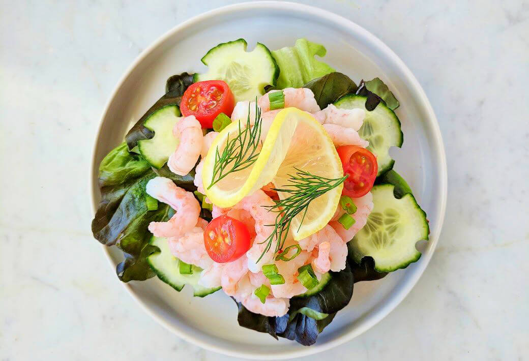Open faced shrimp sandwich piled high with lettuce, cucumbers, cherry tomatoes, shrimp, lemon, and dill.