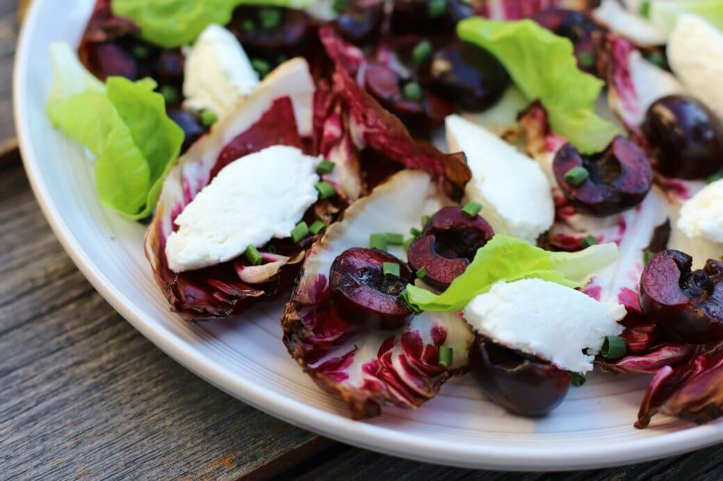 A beautiful salad of grilled radicchio, bright red cherries, green lettuce, and white goat cheese quenelles on a white plate.