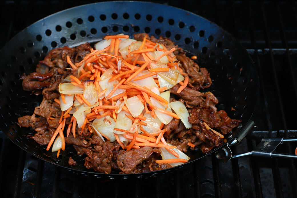 Caramelized beef, onions, and carrots in a grilling basket.