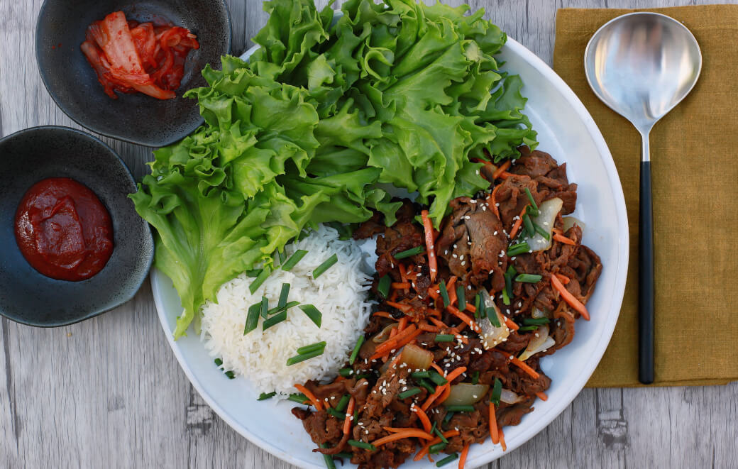 A white plate filled with caramelized beef, rice and green lettuce.