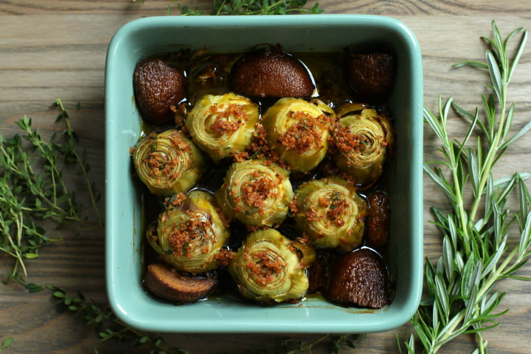 A baking dish full of Roasted Baby Artichokes topped with olive oil, bread crumbs,and Rosemary.