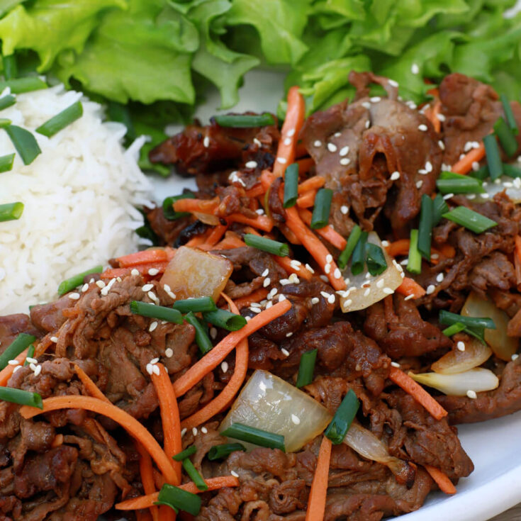 Close up of caramelized beef with carrots,onions, and sesame seeds.