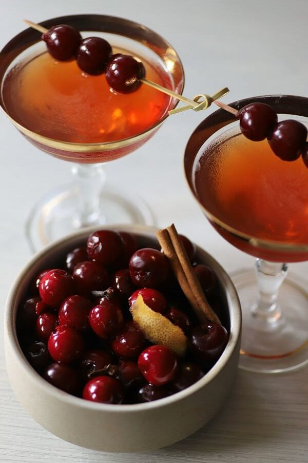 Two Manhattan Cocktails place behind a bowl of cherries.
