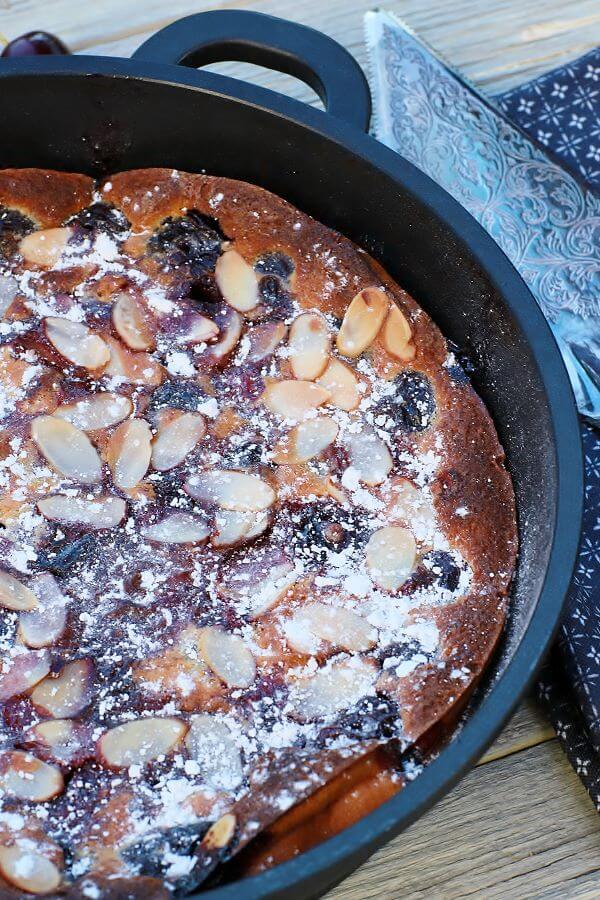 A cast iron pan containing baked cherry clafoutis topped with almonds and powdered sugar.