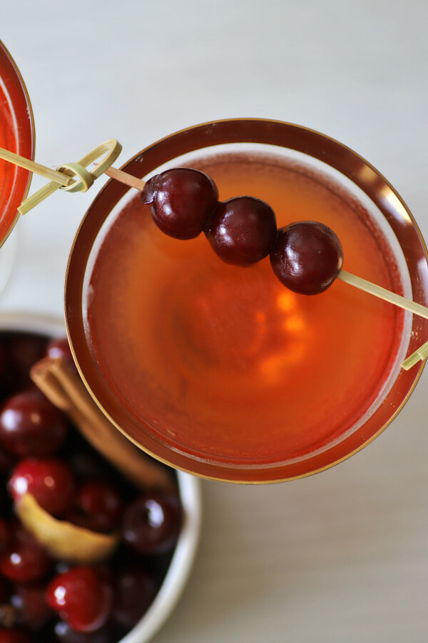 A Manhattan cocktail in a gold rimmed coupe glass garnished with three cherries on a stick.