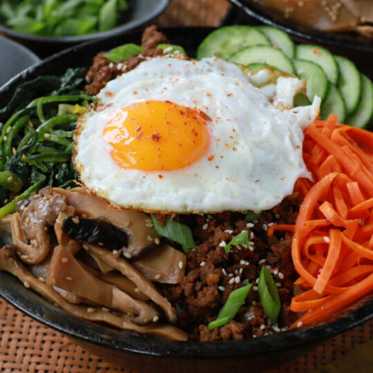 A bowl of vegetables and ground beef topped with an egg.