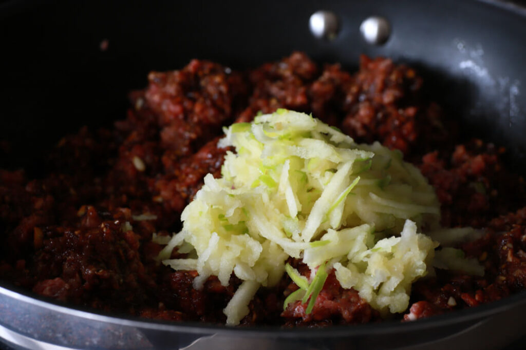 Grated green apple on top of raw spicy ground beef.