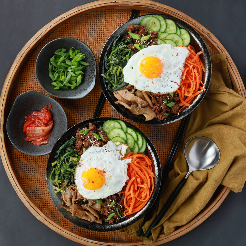 Two bowls of vegetables and ground beef topped with an egg.