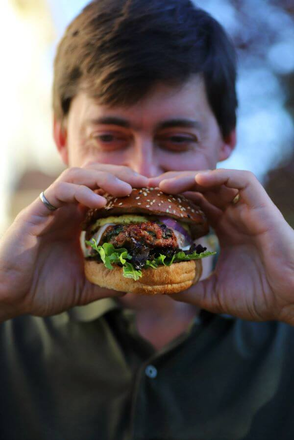 A smiling man holds a loaded Burger in his hands.