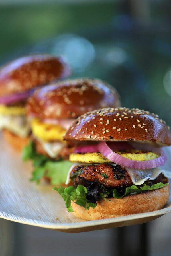 Three Pork Burgers loaded with red onions, grilled pineapple, melted cheese, pork patty and lettuce.
