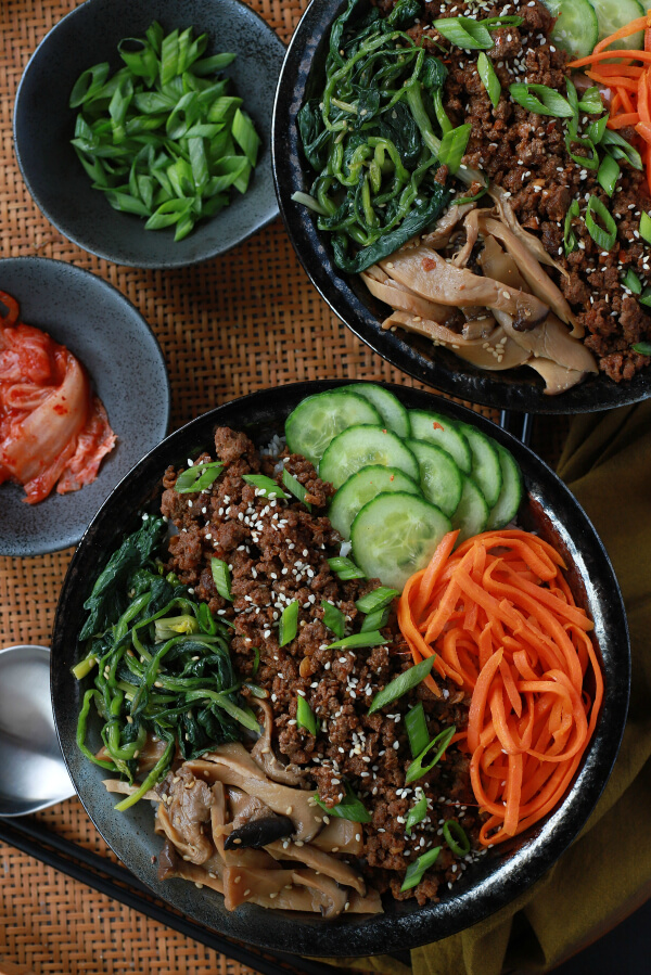 Two bowls of vegetables and ground beef with a side of kimchi.