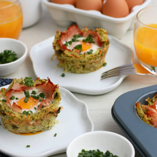 White table scene breakfast setting with Baked Ham and Egg Hash Brown Cups.