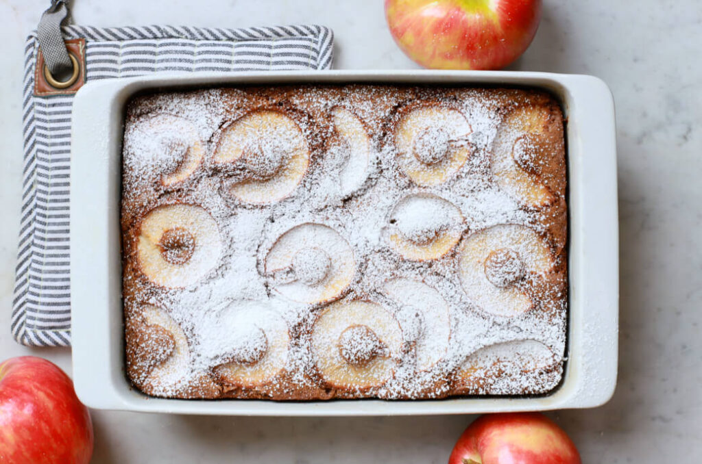 A baked cake topped with apple slices sprinkled with powdered sugar.