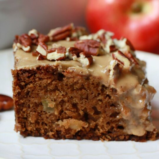 A slice of chunky apple cake topped with brown sugar glaze and pecans.